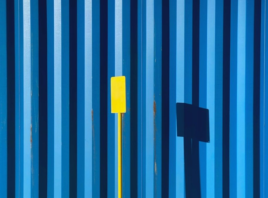 Glenn Homann ~ Yellow Sign, Blue Container, Wires, Clouds
